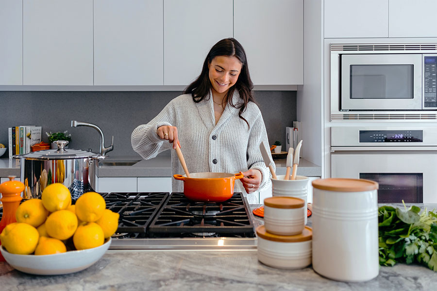Woman cooking in front of her frameless kitchen cabinets