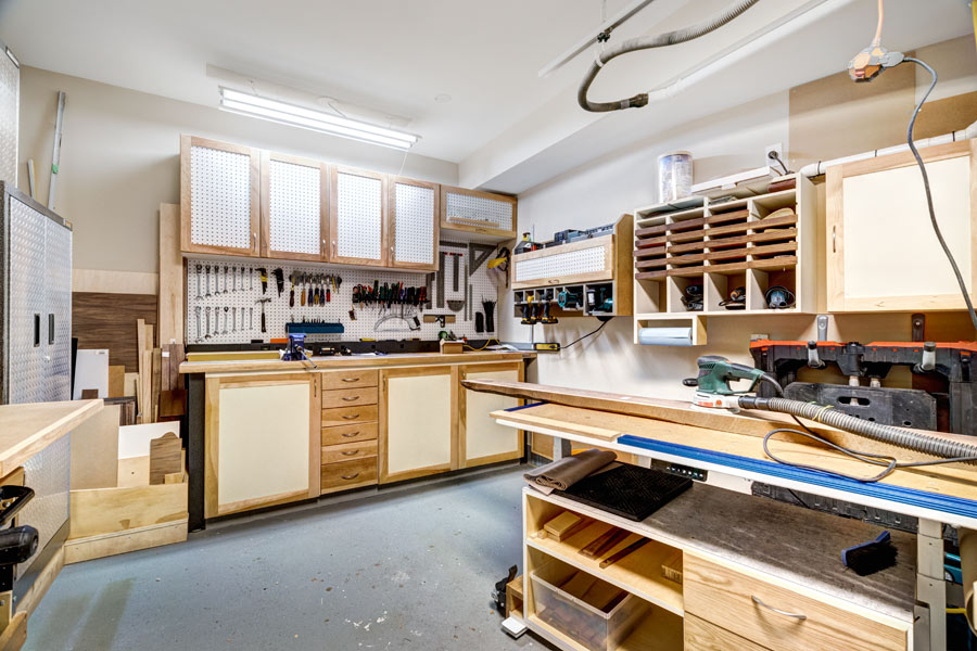 Custom cabinets for your garage will have a different look and feel than the cabinets in your home. Sturdy drawer fronts and doors can also act as peg boards for extra storage.